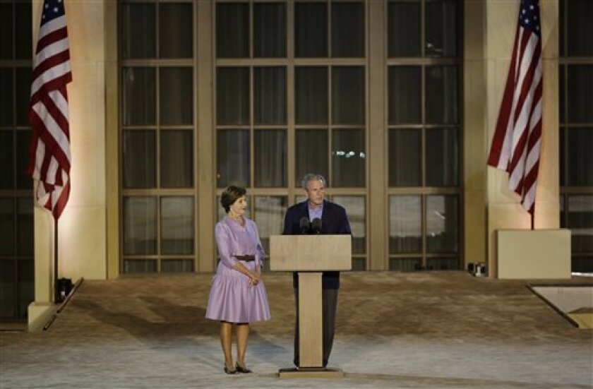 Former president George W. Bush, right, with former first lady Laura Bush, addresses the audience during the lighting of Freedom Hall ceremony at the George W. Bush Presidential Center Thursday, April 25, 2013, in Dallas. (AP Photo/David J. Phillip) (AP Photo/David J. Phillip) .