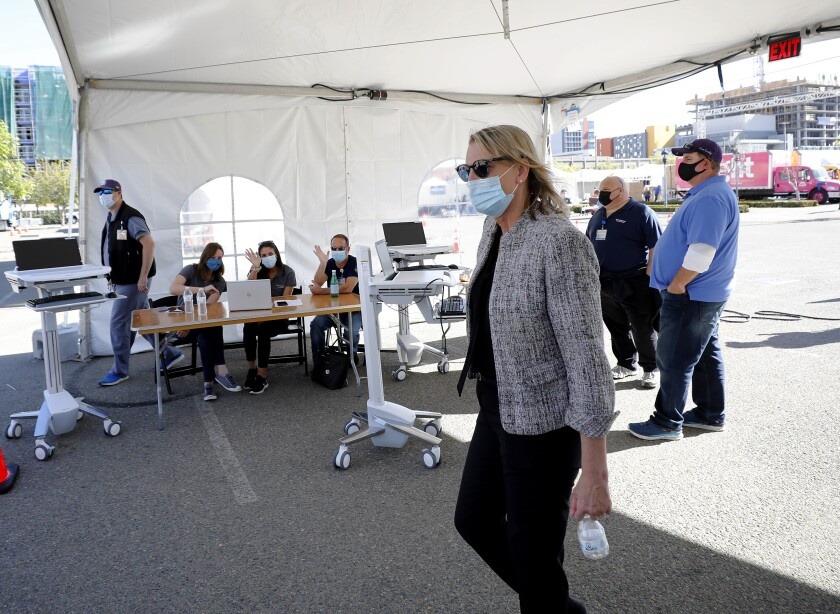 Patty Maysent, CEO of UC San Diego Health, walked through a registration tent at a vaccination super station site.