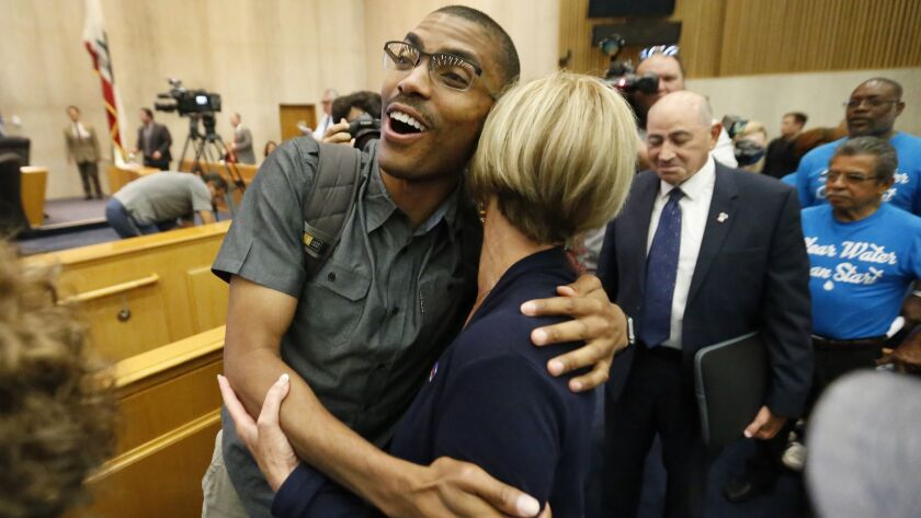 LOS ANGELES, CA – JULY 9, 2018: Compton Commissioner Rodney Andrews, left, hugs Los Angeles Count