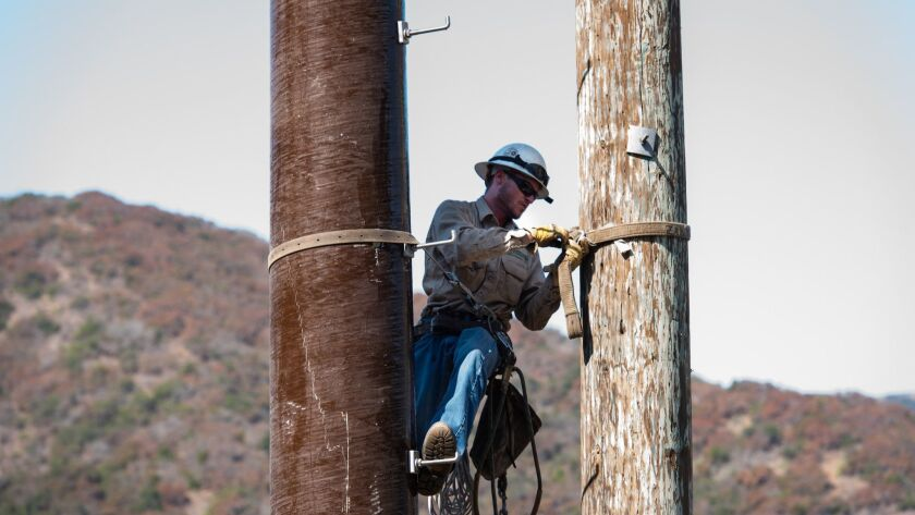 Southern California Edison crews replace wooden poles with fire-resistant composite ones. The utility is weighing whether to proactively shut off power to more than 100,000 customers in the face of wind-driven fire threats.