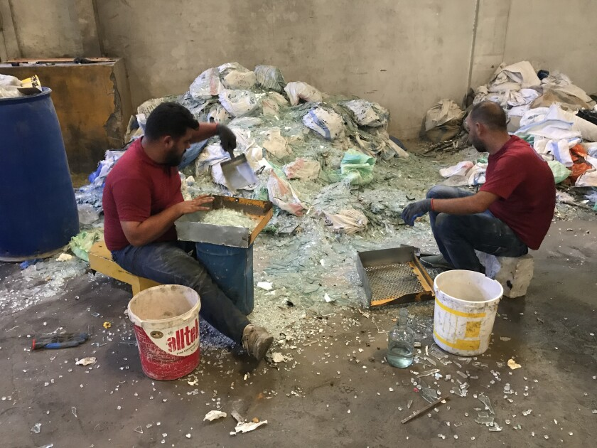 Workers at a factory in Lebanon sort through piles of shattered glass.