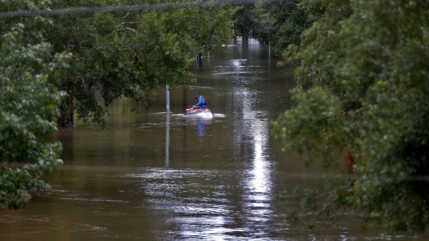 HOUSTON, TEXAS, SUNDAY, AUGUST 27 2017 - Daniel Gross, 15, sits atop a car, waiting to rescue crews