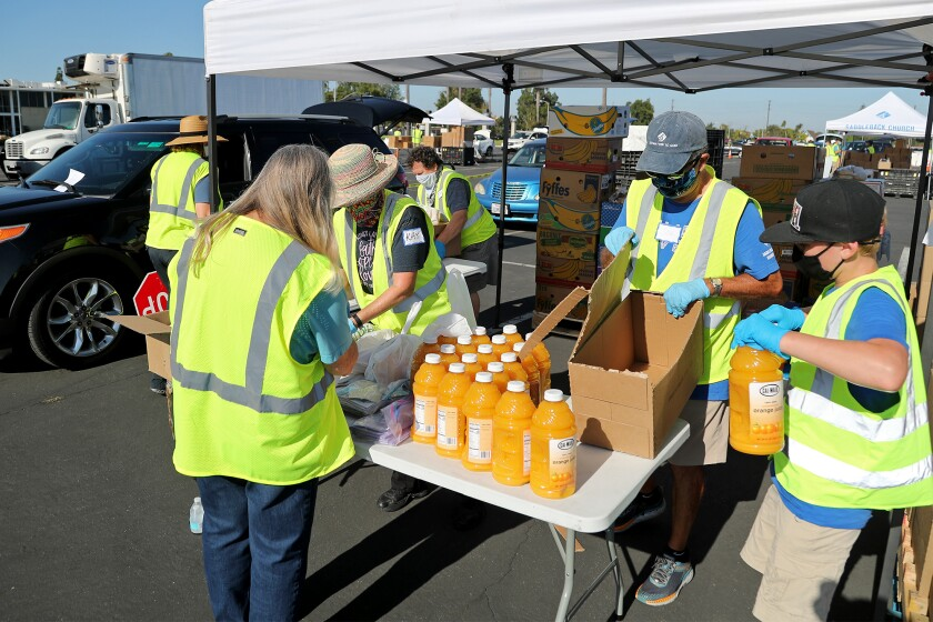 Volunteers sort out bottles of orange juice to give out during a drive-through food distribution event at the OC Fairgrounds.