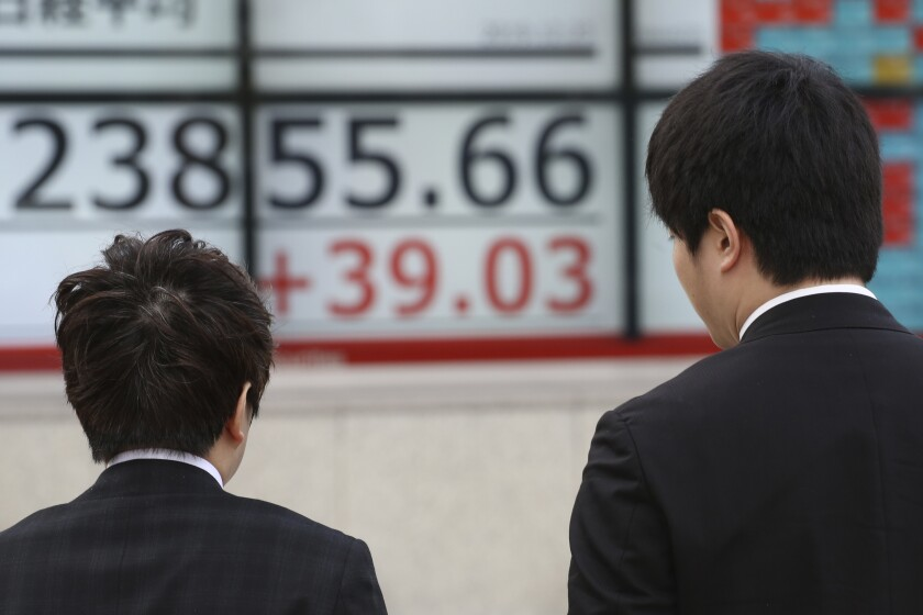 People walk by an electronic stock board of a securities firm in Tokyo, Monday, Dec. 23, 2019. Shares were mixed Monday in quiet trading ahead of Christmas holidays for many markets. (AP Photo/Koji Sasahara)