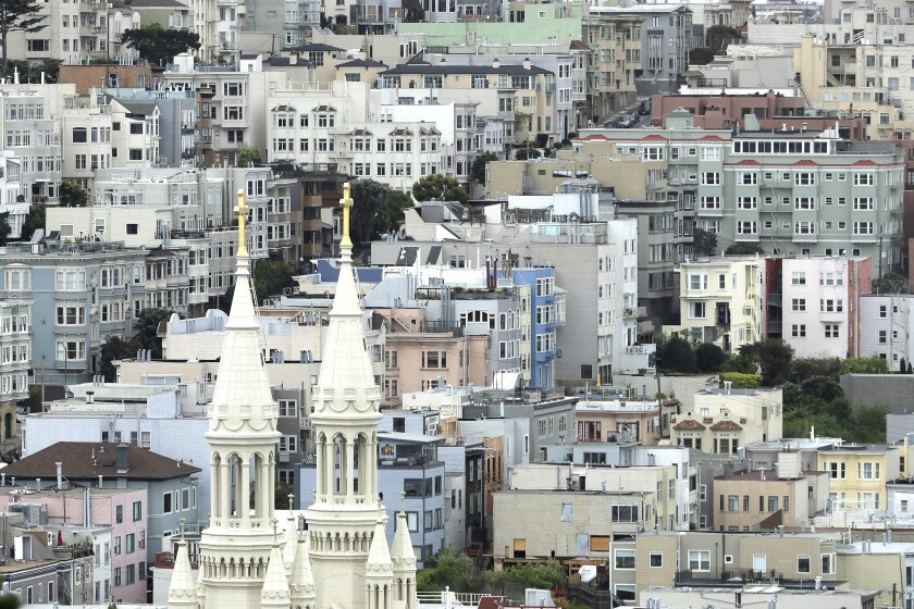 The twin white steeples of Sts. Peter and Paul Church rise amid housing in San Francisco.