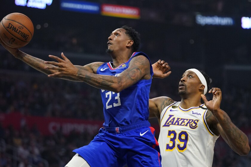 Clippers guard Lou Williams, left, shoots in front of Lakers center Dwight Howard.