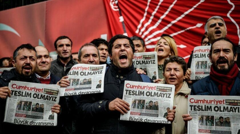Protesters hold copies of the Turkish daily Cumhuriyet during a demonstration outside the newspaper's Istanbul offices in November 2016.