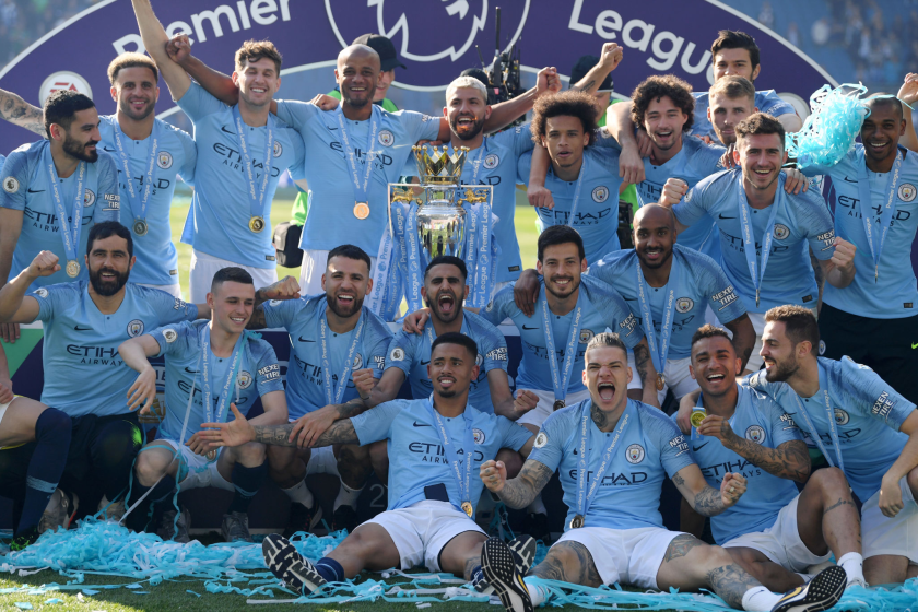Manchester City players celebrate with the Premier League Trophy.