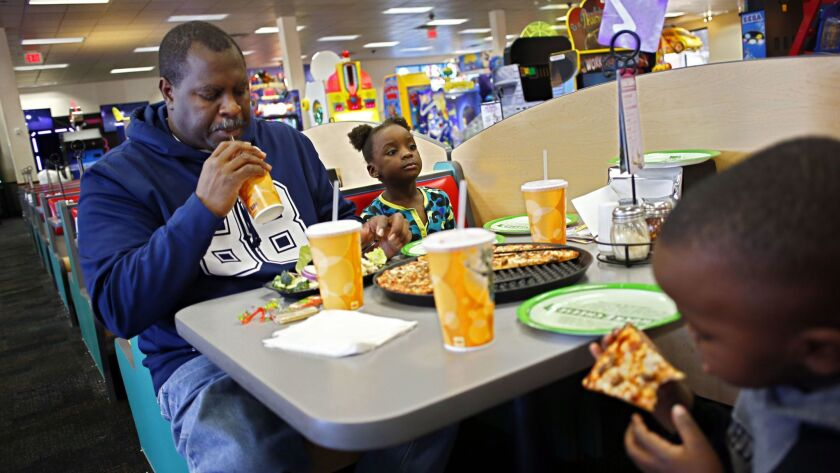 FILE- This Jan. 16, 2014, file photo shows from left, Larry Roberson eats lunch with his grandchildr