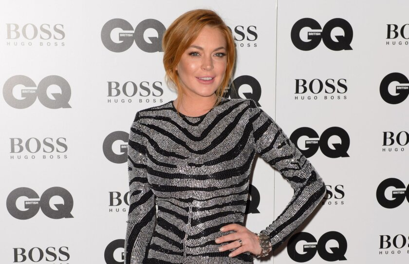 FILE- In this Sept. 2, 2012 file photo, Lindsay Lohan arrives for the GQ Men Of The Year Awards 2014 at a venue in central London. A Los Angeles court on Wednesday, Feb. 18, 2015, delayed a hearing in which further details about Lohan's community service were scheduled to be presented due to a pros