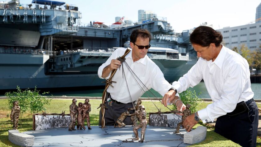 Frank Powell (left) and his brother Mark set up a model of the proposed memorial in Tuna Harbor Park in August 2015. Several of the design elements have changed but not the large piece of barbed wire in the center.