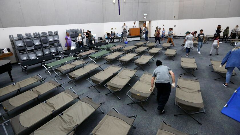 Cots are set up for the homeless to sleep on after a church service in the chapel at the Union Rescue Mission on skid row. The homeless shelter, designed for 890 people, takes in about 1,300 every night, using the chapel for overflow.