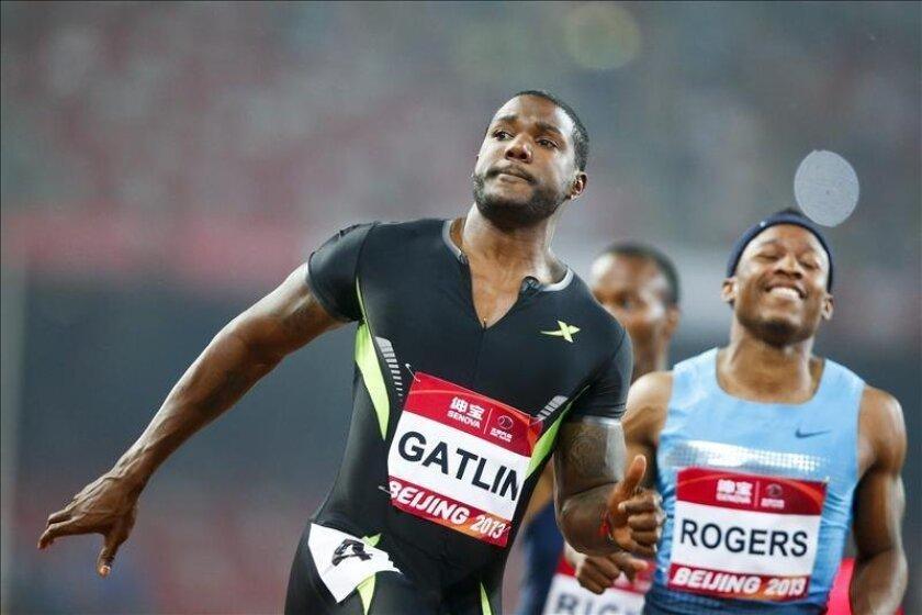 El atleta estadounidense Justin Gatlin (i) cruza la línea de meta por delante del también estadounidense Michael Rogers (d) durante la carrera de 100 metros de la reunión de Pekín. EFE