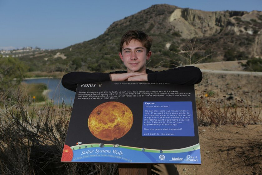 Colton Dister, 16, shows the Venus panel of his solar system exhibit at Lake Calavera Preserve in Carlsbad Thursday.