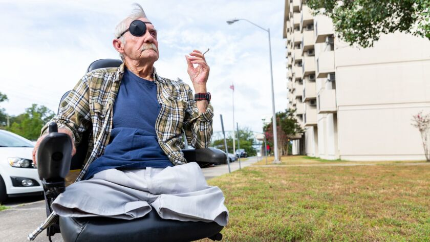 Billy Brooks smokes a cigarette in front of the public housing building where he lives in Wilmington