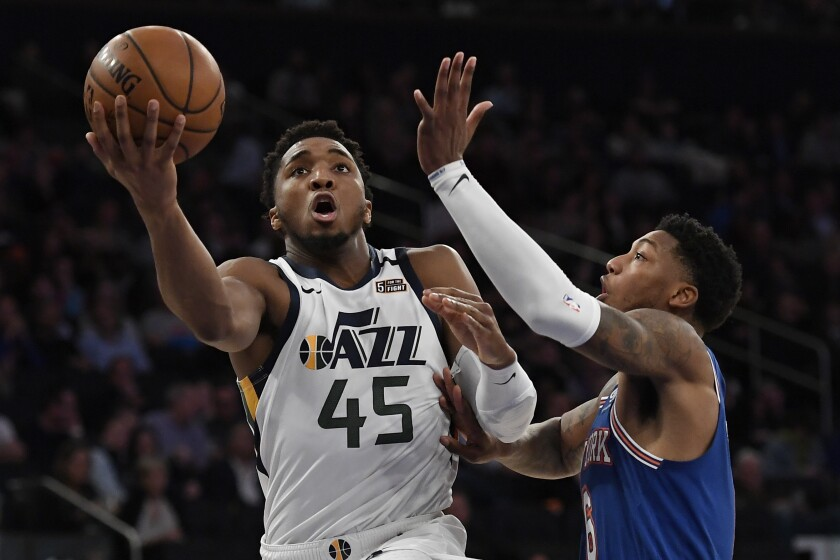 Utah Jazz guard Donovan Mitchell (45) shoots next to New York Knicks guard Elfrid Payton during the second half of an NBA basketball game in New York, Wednesday, March 4, 2020. (AP Photo/Sarah Stier)