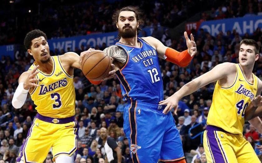 Josh Hart (i) de Los Angeles Lakers en acción ante Steven Adams (c) de Oklahoma City Thunder este jueves, durante un partido de baloncesto de la NBA entre Los Ángeles Lakers y Oklahoma City Thunder, en el Chesapeake Energy Arena de Oklahoma (EE.UU.). EFE