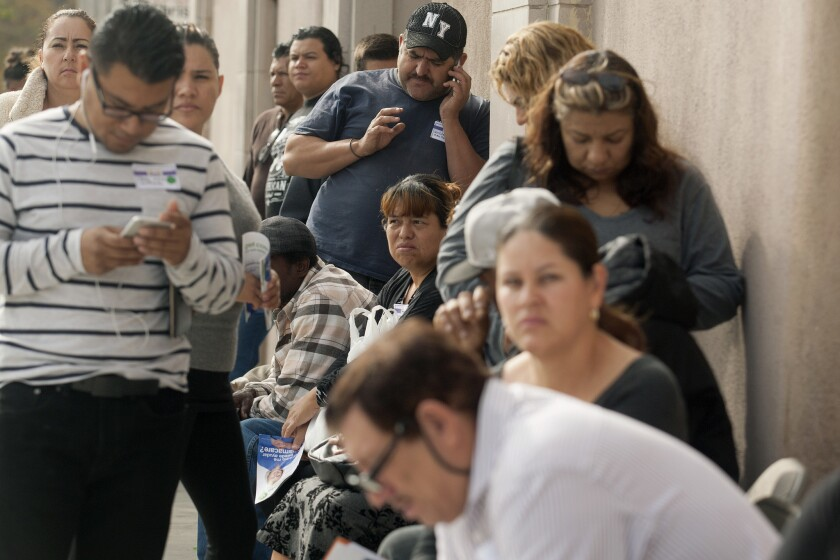 Los Angeles residents line up to enroll in Covered California and Medi-Cal plans on Nov. 15, 2014. The following week, advocates filed suit against the state challenging the legality Medi-Cal's renewal process.