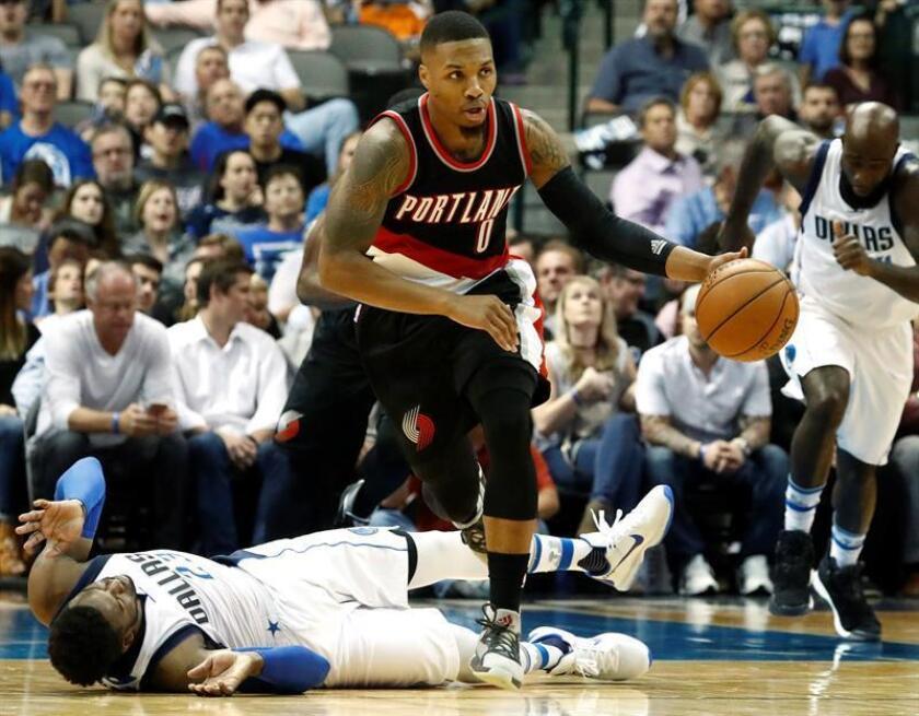 El jugador de Portland Trail Blazers Damian Lillard (dcha) le roba la pelota al jugador de los Dallas Mavericks Wesley Matthews (izda) en la primera mitad de un partido de baloncesto de la NBA. EFE