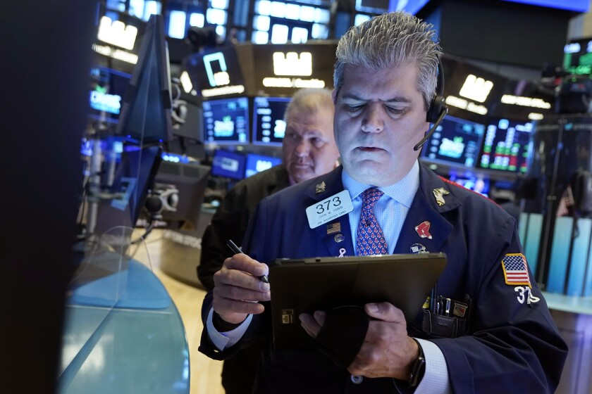 Trader John Panin, foreground, works on the floor of the New York Stock Exchange, Friday, July 23, 2021.