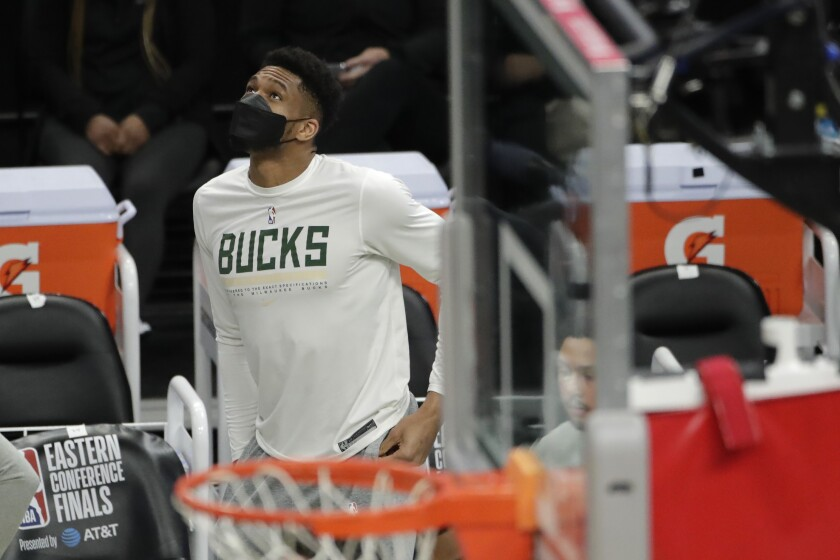 Milwaukee Bucks' Giannis Antetokounmpo looks up to the scoreboard from the bench during the second half of Game 5 of the team's NBA basketball playoffs Eastern Conference finals against the Atlanta Hawks on Thursday, July 1, 2021, in Milwaukee. (AP Photo/Aaron Gash)