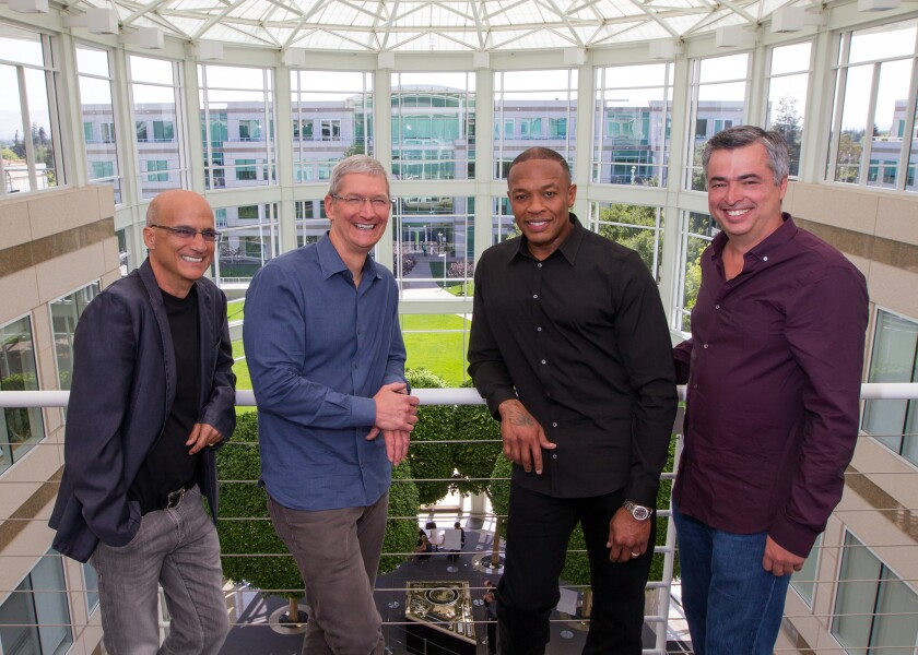 Music entrepreneur and Beats co-founder Jimmy Iovine, left, Apple CEO Tim Cook, Beats co-founder Dr. Dre and Apple Senior Vice President Eddy Cue gather at Apple's headquarters in Cupertino, Calif.