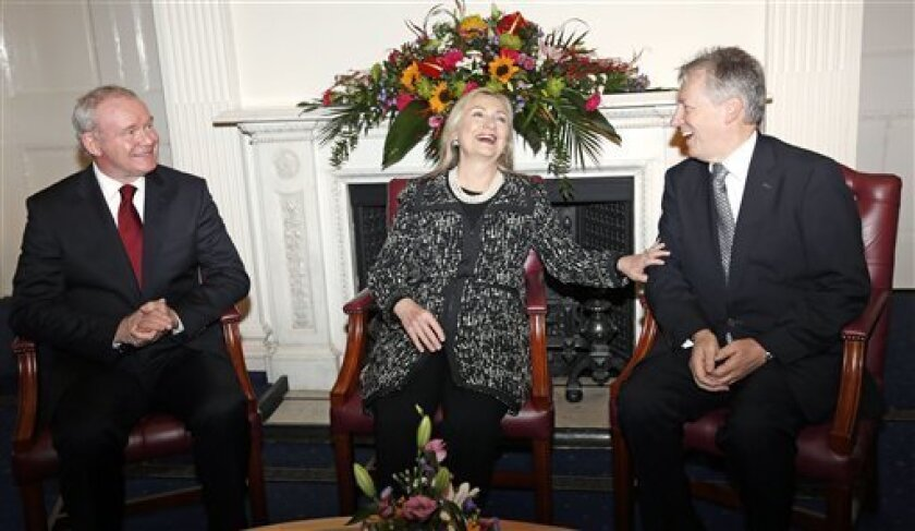 U.S. Secretary of State Hillary Rodham Clinton, centre, reacts with Northern Ireland's First Minister Peter Robinson, right, and Deputy First Minister Martin McGuinness, left, at Stormont Castle in Belfast, Northern Ireland, Friday, Dec. 7, 2012. Clinton travelled to Northern Ireland on Friday to lend her support to the British province's fragile peace, the frailty of which was underlined by overnight rioting on the eve of her visit and the seizure of a bomb. (AP Photo, Kevin Lamarque, Pool)
