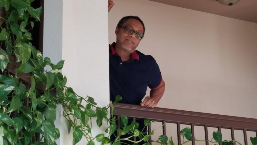 A man leans against a banister