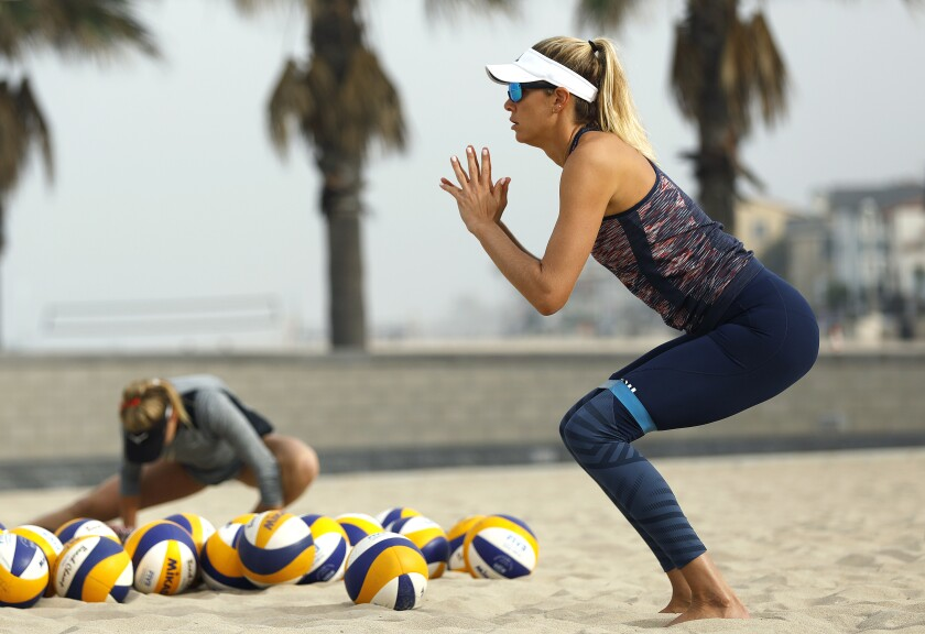 April Ross and Alix Klineman, right, get warmed up for practice in Hermosa Beach in preparation for the AVP Manhattan Beach Open on Tuesday.
