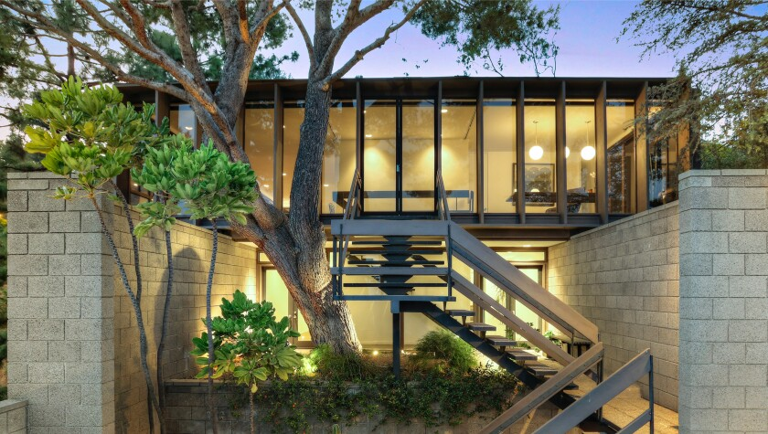 Built in 1966, the 2,300-square-foot home takes in sweeping city views through walls of glass.