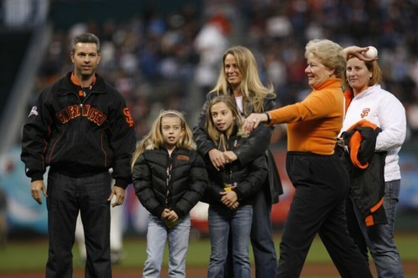 Sue Burns throws the first pitch at a Giants game in 2007 in honor of her husband, Harmon Burns, who had died the previous year. The team says the part-owner attended at least 1,000 games in the last decade, usually dressed in orange.
