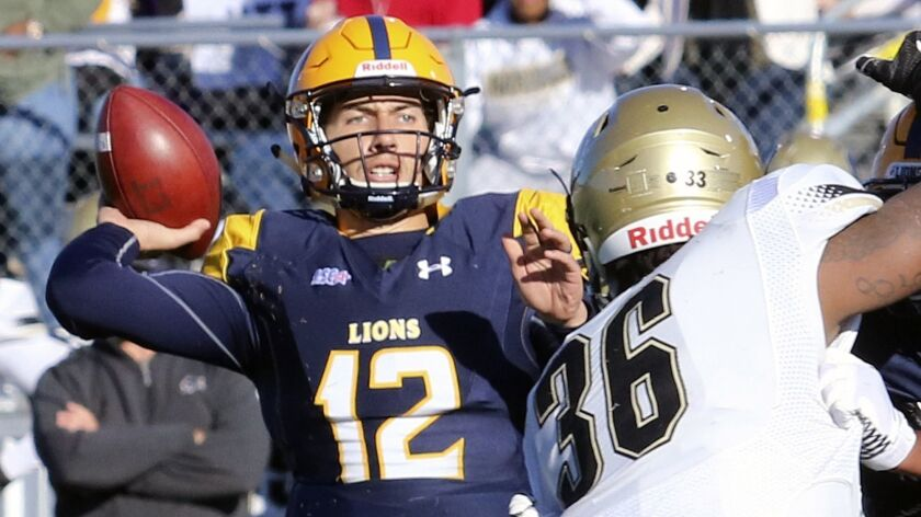 Texas A&M-Commerce quarterback Luis Perez (12) throws under pressure from Harding defender Shedrick