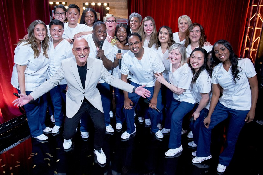 Howie Mandel with singers attired in white shirts and blue jeans