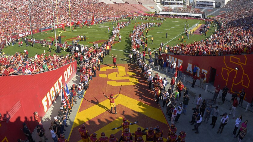 USC football players run onto the field at the Coliseum before a game.