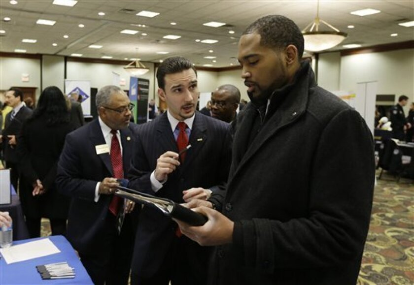In this Feb. 28, 2013 photo Robin Basil, left, of the Garland-Hill insurance agency talks with college student Markell Easter at the JobFairGiant.com employment fair in Dearborn, Mich. Fewer Americans sought unemployment aid last week, reducing the average number of weekly applications last month to a five-year low. The drop shows that fewer layoffs are strengthening the job market. The Labor Department said Thursday, March 14, 2013 that applications fell 10,000 to a seasonally adjusted 332,000.