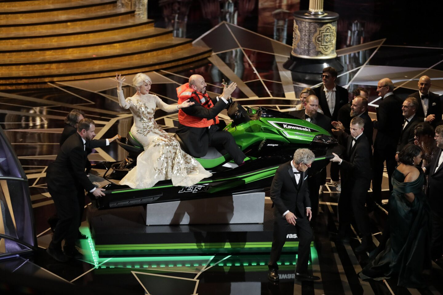 """Costume designer Mark Bridges (""""Phantom Thread""""), with Helen Mirren in tow, rides onstage with the jet ski he won for having the fastest winners' speech during the telecast of the 90th Academy Awards."""