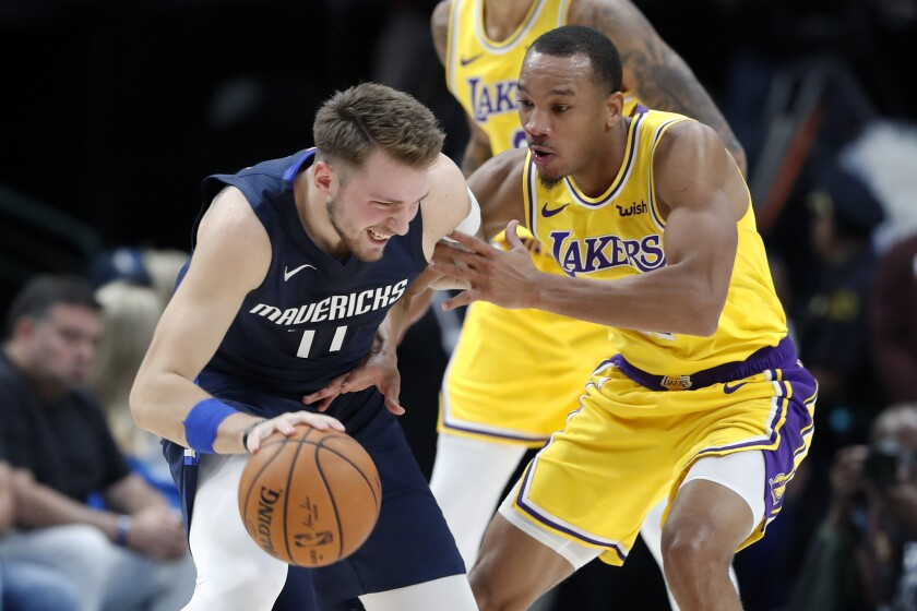 Lakers guard Avery Bradley defends Mavericks guard Luka Doncic during game earlier this season.