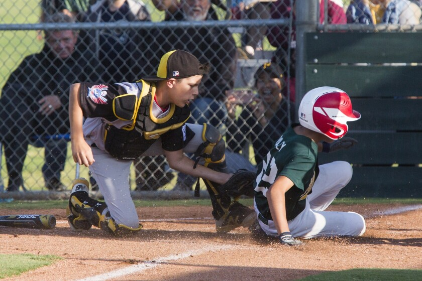 From left, Costa Mesa National's Cooper Cirillo tags out Costa Mesa American's Michael Buley during