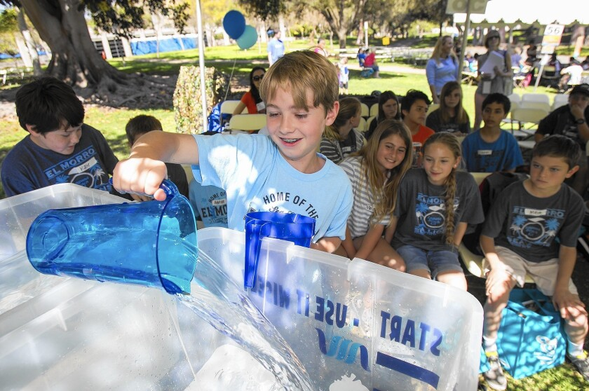 Christian Yates, 11, from El Morro Elementary in Laguna Beach, pours water from one plastic container to another at Mesa Water's booth during the 2015 Children's Water Education Festival at UC Irvine on Wednesday.