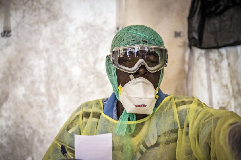 In this photo taken Monday, Aug. 11, 2014, a health worker examines patients for Ebola inside a screening tent, at the Kenema Government Hospital situated in the Eastern Province around 300 km, (186 miles), from the capital city of Freetown in Kenema, Sierra Leone. Over the decades, Ebola cases have been confirmed in 10 African countries, including Congo where the disease was first reported in 1976. But until this year, Ebola had never come to West Africa. (AP Photo/ Michael Duff)