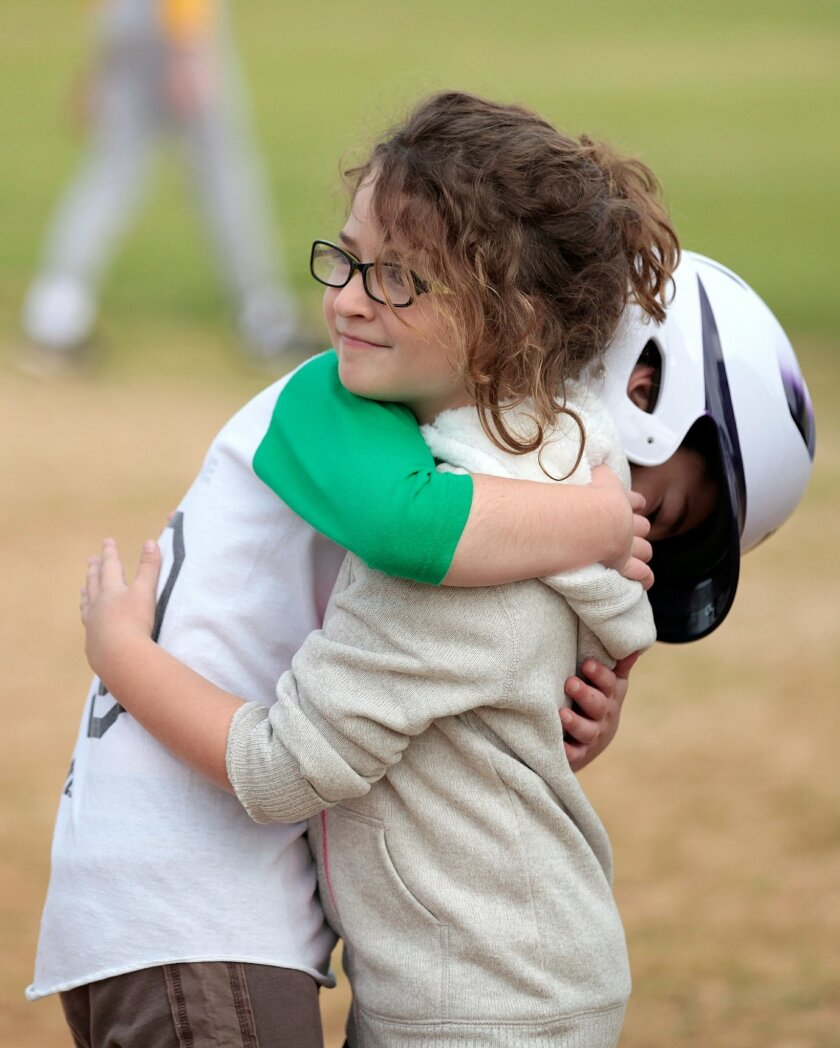 Paul Rosenberg, 9, of the Lunging Lizards thanks his younger sister Brooke Rosenberg for getting him to first base during an adapted baseball game in the Autism Baseball League in Rancho Penasquitos Saturday.