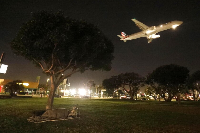 A homeless person sleeps in a park at the corner of W. 92nd Street and Sepulveda Blvd. as a plane comes in for a landing at the Los Angeles International Airport in Westchester.