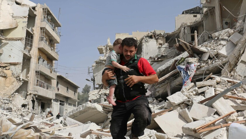A Syrian man carries a child after removing him from the rubble of a destroyed building following a reported airstrike in the Qatarji neighborhood of the northern city of Aleppo on Wednesday.