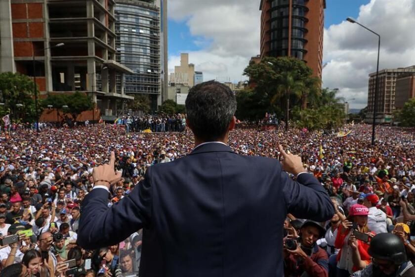 El presidente del Parlamento venezolano, Juan Guaidó (c), saluda a manifestantes tras anunciar que asume las competencias del Ejecutivo, en Caracas (Venezuela). EFE