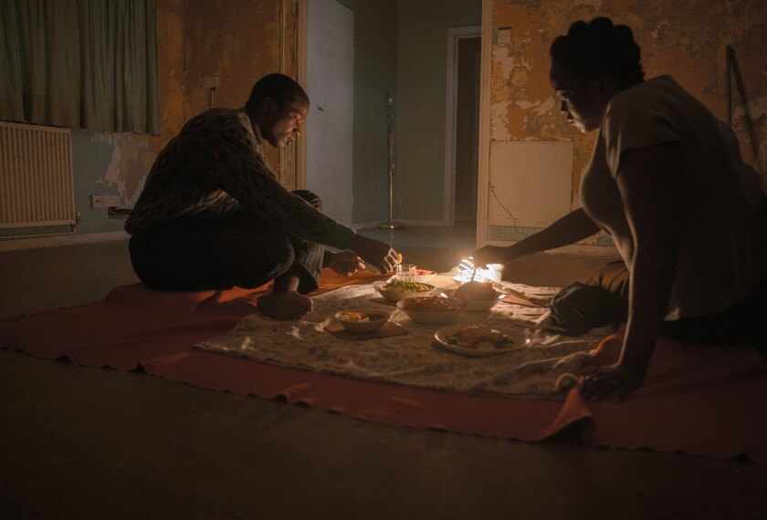 "Ṣọpẹ́ Dìrísù, left, and Wunmi Mosaku eat dinner on the floor of their new home in ""His House."""