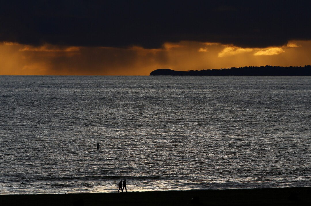 A couple walks alone on Santa Monica Beach as rain falls from storm clouds in the distance.