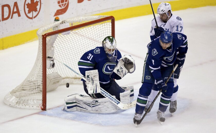 Vancouver Canucks goalie Eddie Lack, left, of Sweden, allows a goal to Tampa Bay Lightning's Valtteri Filppula, not seen, while being screened by Alex Killorn, top right, as Canucks' Chris Tanev defends during the second period of an NHL hockey game Wednesday, Jan. 1, 2014, in Vancouver, British Columbia. (AP Photo/The Canadian Press, Darryl Dyck)