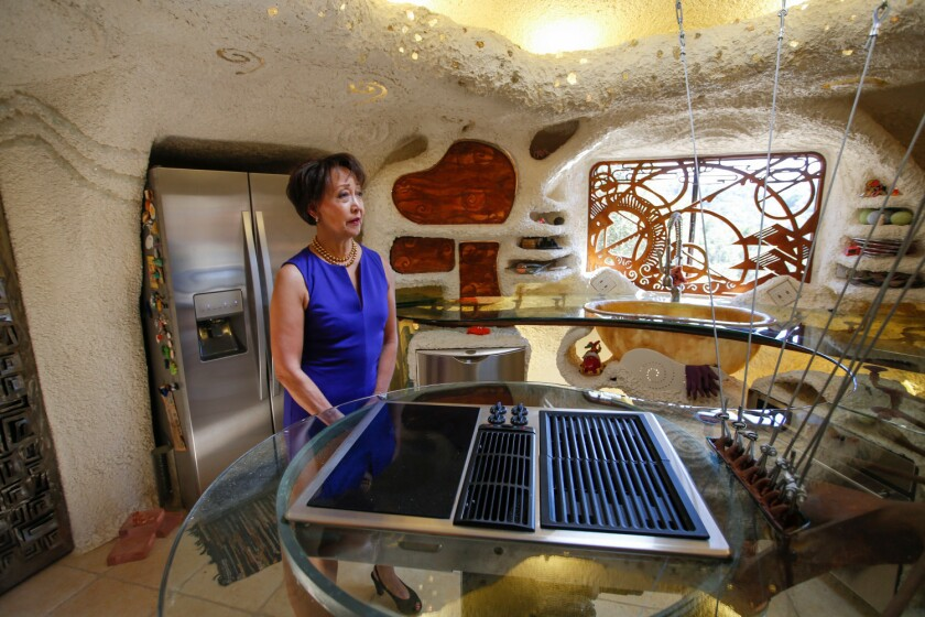 Real estate agent Judy Meuschke stands in the kitchen of the home known as the Flintstone House in Hillsborough.