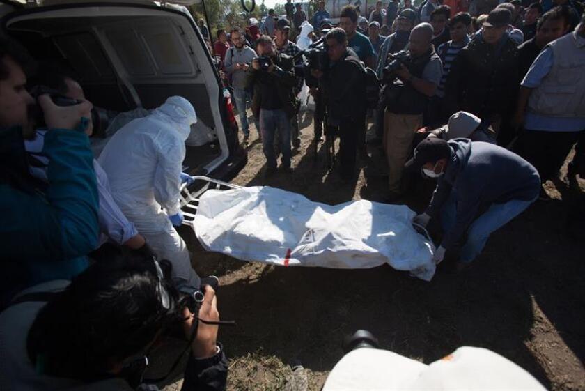 Expertos forenses registran la zona cerca de una toma clandestina de gasolina de Petróleos Mexicanos (Pemex) que explotó este sábado, en Tlahuililpan, Hidalgo (México). EFE/MLA