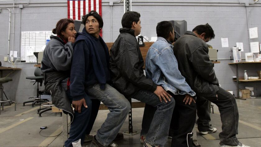 A group of migrants await processing in a U.S. Border Patrol detention center in Nogales, Arizona.